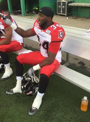 2015 Jackets In The Pros Archives, Tory Harrison, Calgary Stampeders, Tory Harrison #34 of the Calgary Stampeders takes a breather during the game between the Calgary Stampeders and Saskatchewan Roughriders in week 9 of the 2015 CFL season at Mosaic Stadium on August 22, 2015 in Regina, Saskatchewan (Photo courtesy of Brent Just) Carver Heights Quarterback Club, Leesburg High School, Leesburg, Florida
