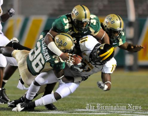 2009 Jackets In College Football Archives, Running Back #11 Tory Harrison (Leesburg High School, Leesburg Florida) is gang-tackled by UAB defenders Elliott McGaskin (36), Daniel White (34) and Hiram Atwater early in Thursday night's game at Legion Field. (The Birmingham News / Frank Couch) comeback. (AP), Carver Heights Quarterback Club, Leesburg High School, Leesburg, Florida.
